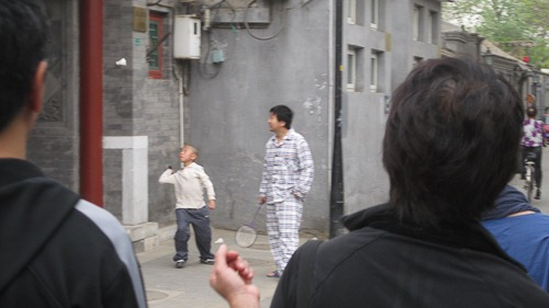 Man playing badminton in his pajamas.