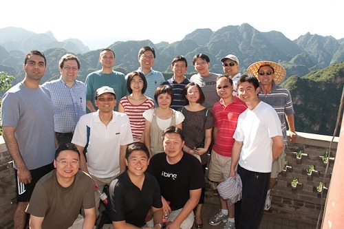 Team photo with seventeen people, mountains in the back.