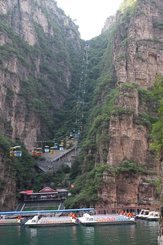 Gondolas go over the water and up a between two cliffs. The water and boats are below.