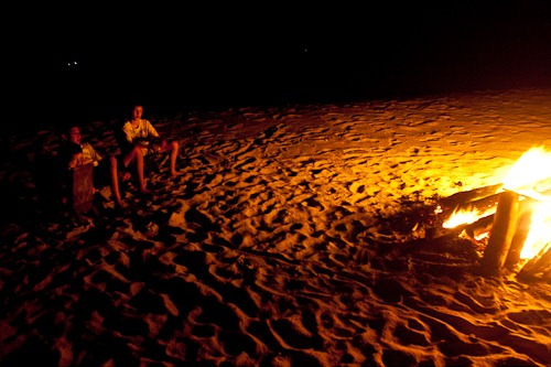 Kids sitting near the huge fire on the beach.
