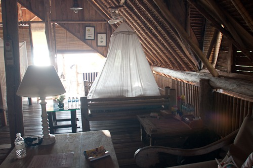 Shot of the inside of the bungalow. Big mosquito netting tent over the bed.