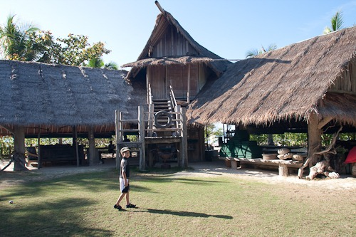 Michael standing in front of a two story thatched roof building with open sides.