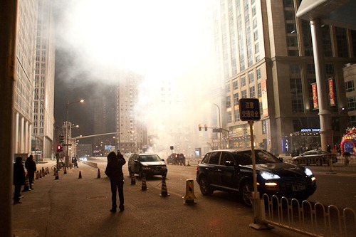 Bright white explosions and smoke in front of The Place in Beijing.