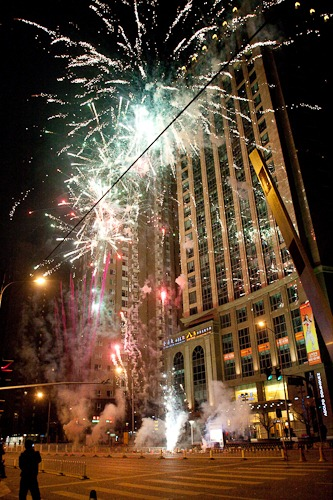 Street-level shot of fireworks exploding very close to buildings in Beijing.