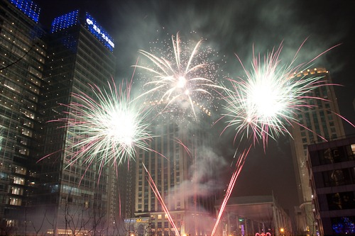 Three way star-burst fireworks in between buildings in Beijing.
