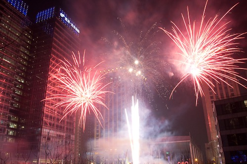 A fountain with two star-burst fireworks in between buildings in Beijing.