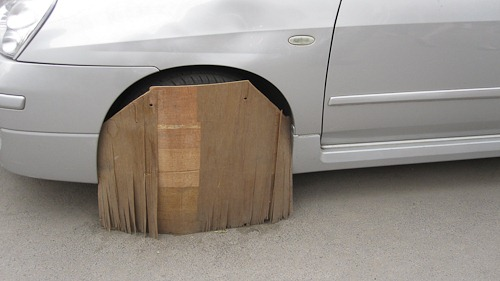 Car tire protected with a wooden board.