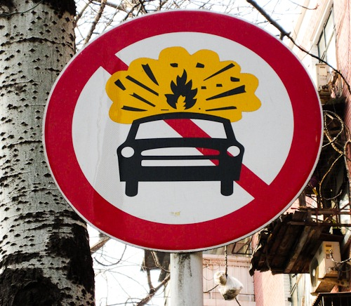 Street sign of a car with a yellow explosion over it, with the big red slash across the whole thing.