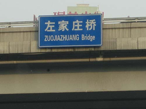 "Sign in Chinese and Pinyin saying ""Zuojiazhuang Bridge""."