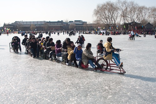 A line of ice chair riders pulled by a bike.